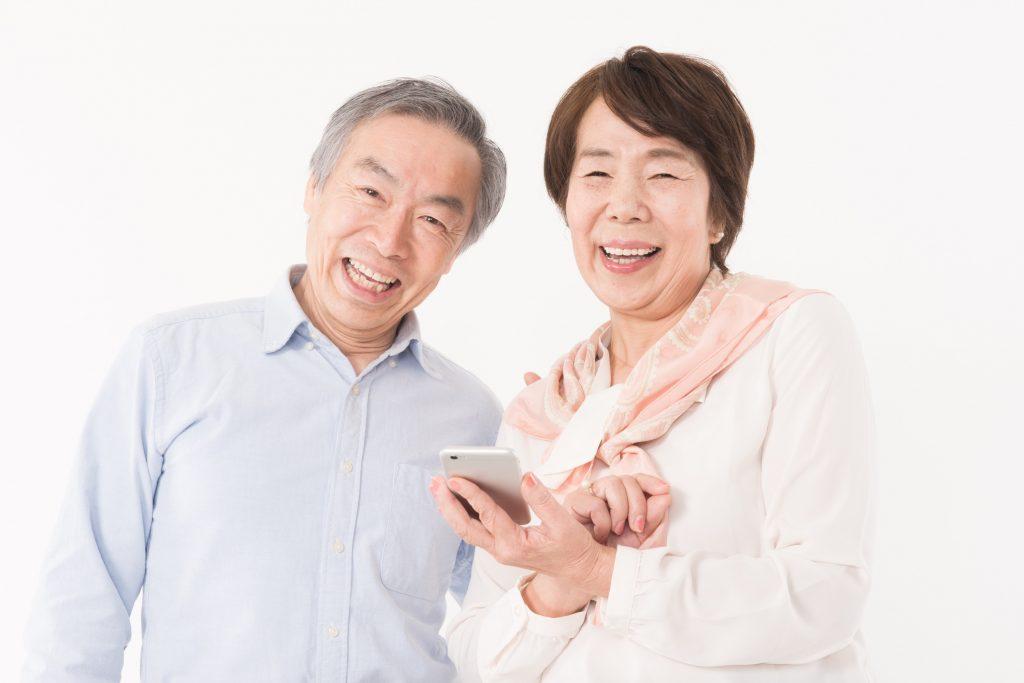 スマホを持って笑顔の夫婦