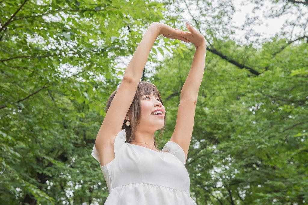 自然の中で伸びをする女性