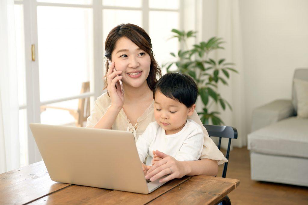 電話をするお母さんとパソコンを見る子供