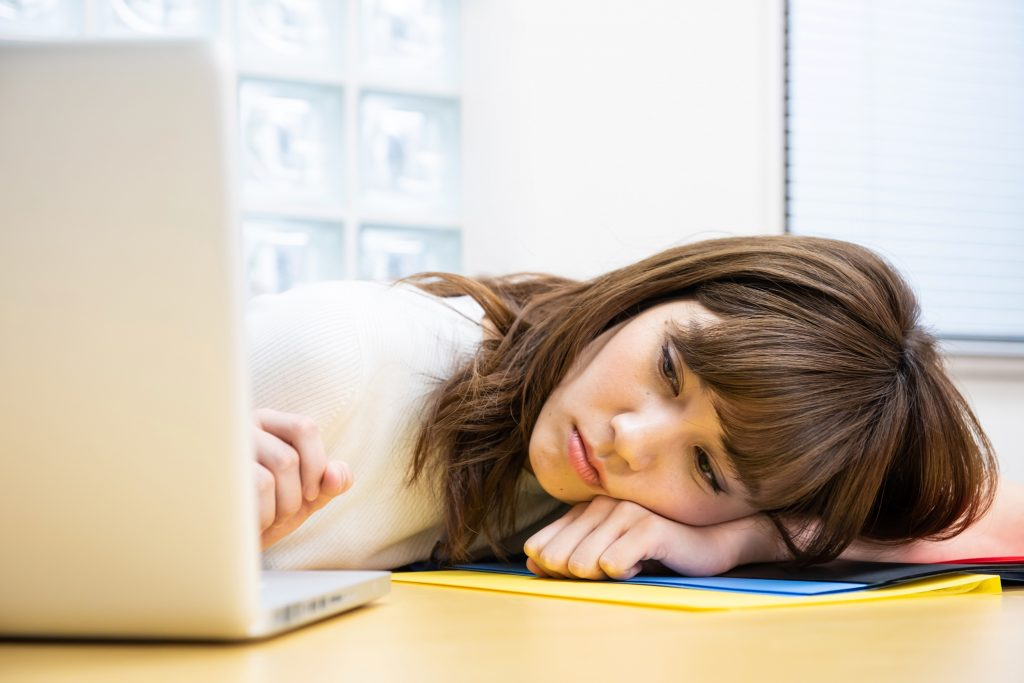 頭をねかせてパソコンを見る女性