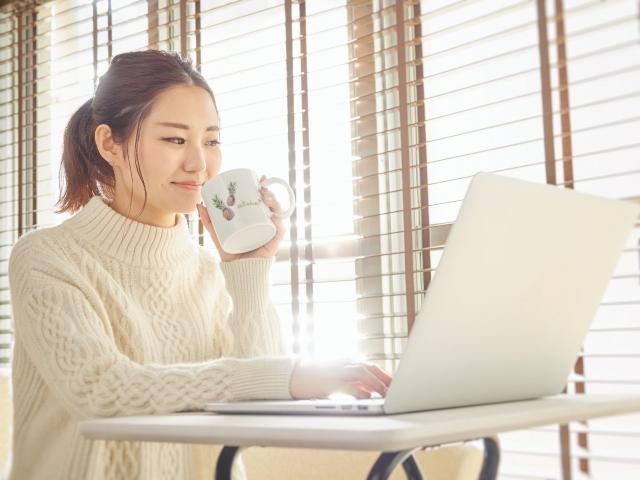コーヒーを飲みながらパソコンをさわる女性