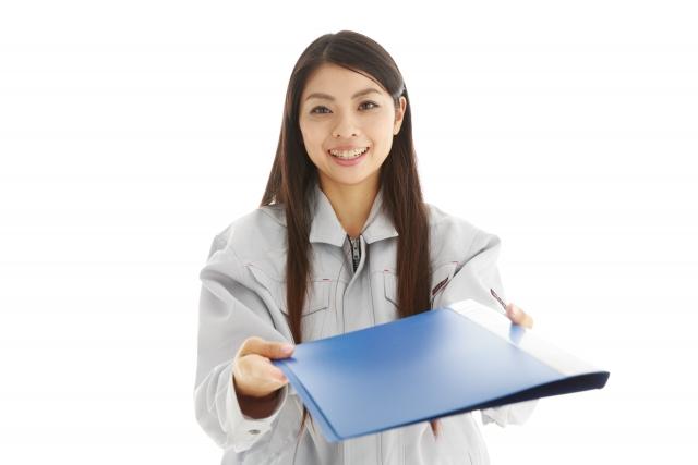 ファイルを持つ作業服の女性