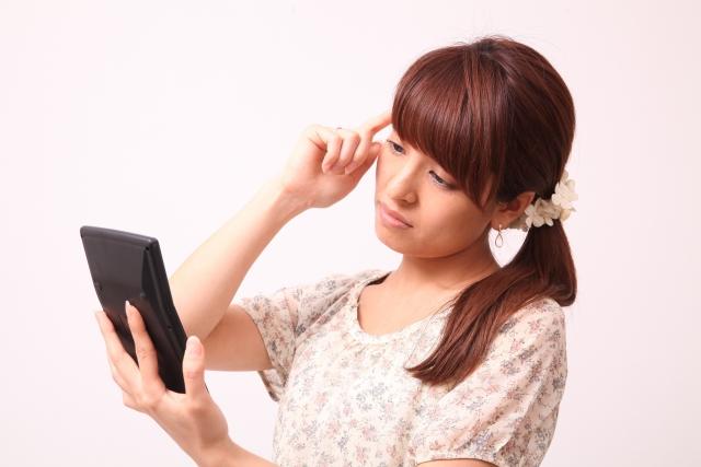 電卓を見て考える女性
