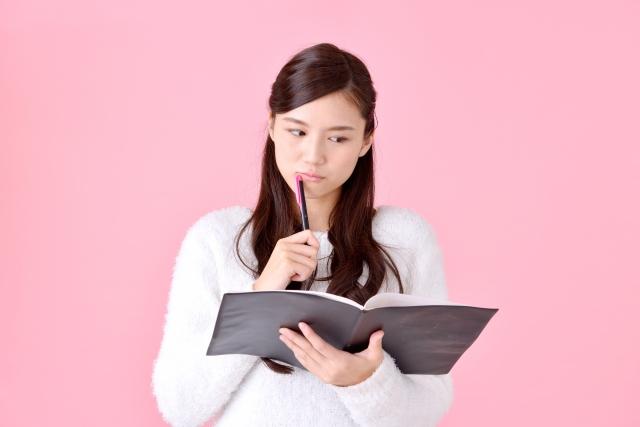 ノートを見て考える女性