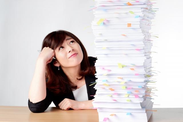 山積みの書類を見る女性