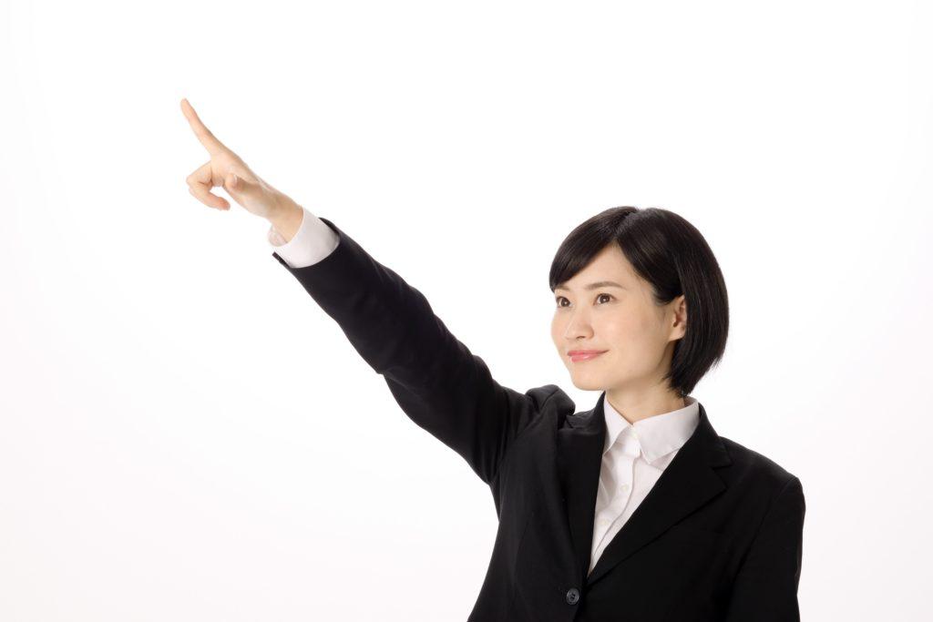 上を指すスーツの女性